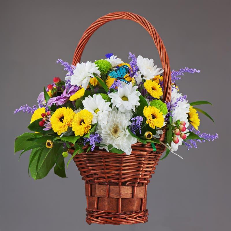 Colorful flower bouquet arrangement centerpiece in wicker basket. On grey background. Closeup stock photography