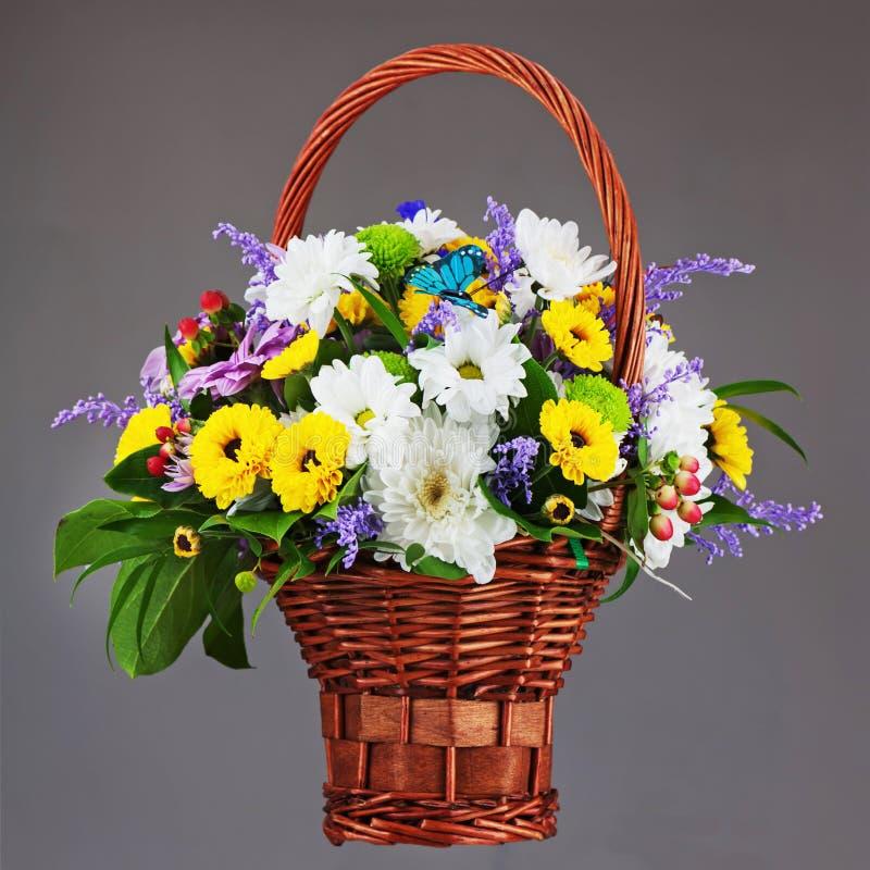 Colorful flower bouquet arrangement centerpiece in wicker basket. On grey background. Closeup stock photos