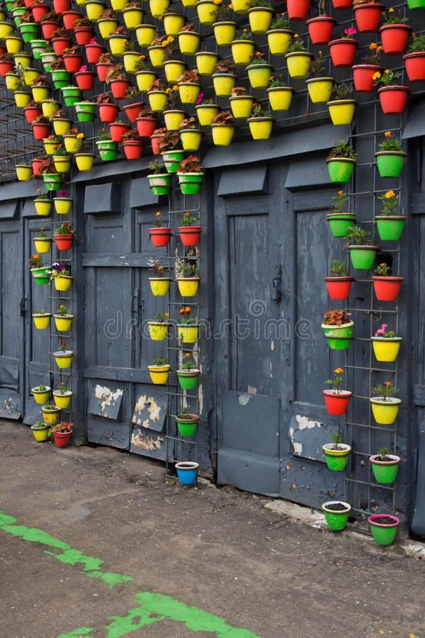 Colorful flower pots on the wall of building. Colorful flower pots on the wall of a building stock photos