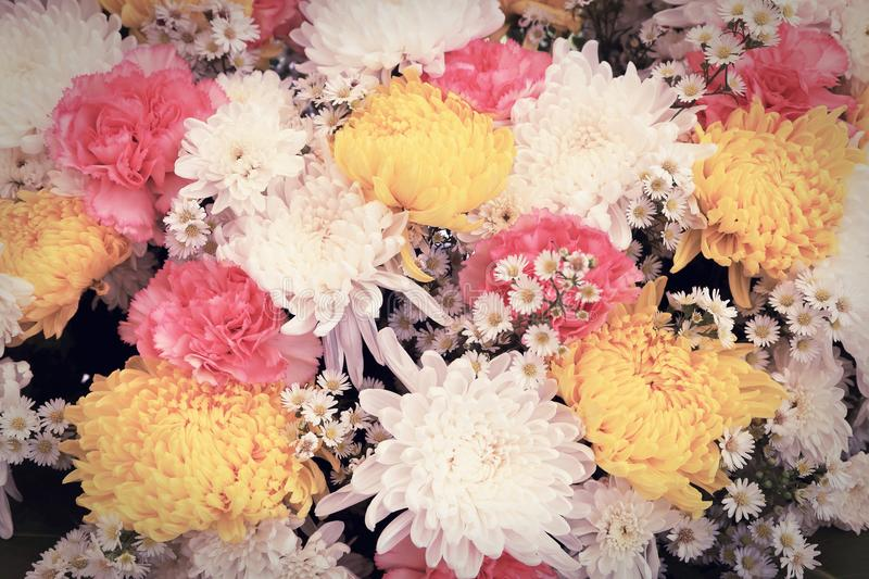 Colorful flowers arranged as a natural background image with white, yellow and pink blossoms. Vintage toned floral bouquet stock images