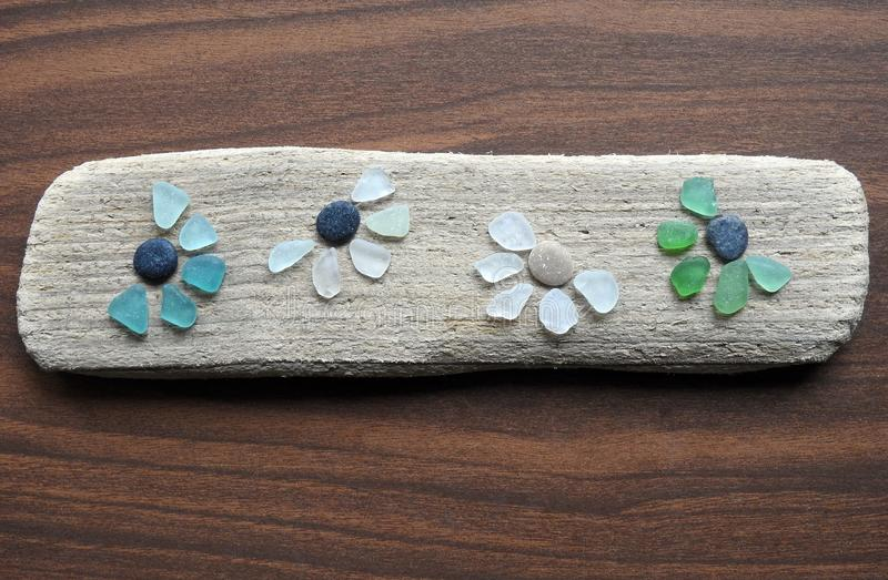 Colorful flowers made from sea glass on sea wood, Lithuania stock photos