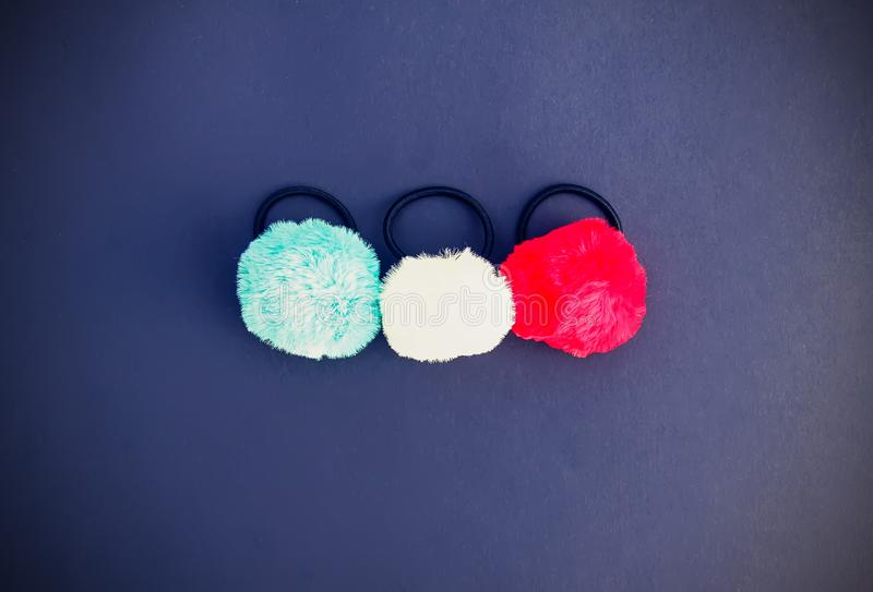 Colorful fluffy pompons on bright background. Fashion decoration festive template. Colorful fluffy pompons on bright background. Fashion decoration festive stock photos