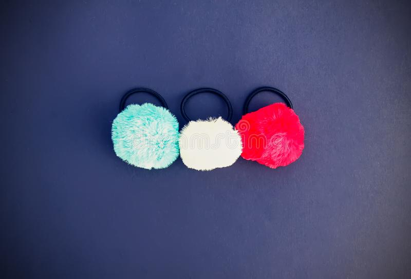 Colorful fluffy pompons on dark background. Fashion decoration festive template. Colorful fluffy pompons on black background. Fashion decoration festive stock images