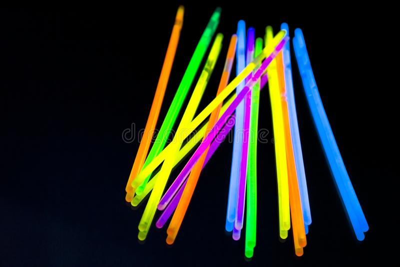 Colorful fluorescent light neon big glow stick on mirror reflection black background. Colorful fluorescent light neon glow stick on mirror reflection black stock photo