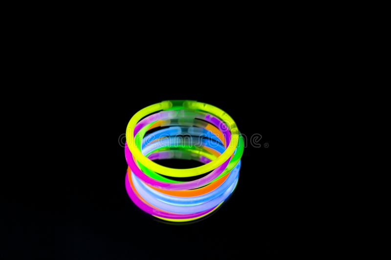 Colorful fluorescent light neon glow stick bracelet strap wristband on mirror reflection black background. Yellow Blue pink orange green violet glow sticks royalty free stock images