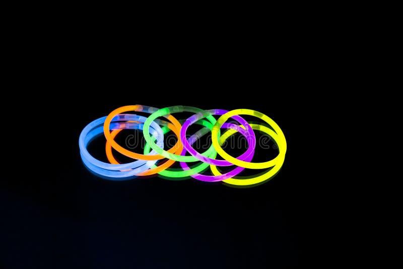 Colorful fluorescent light neon glow stick bracelet strap wristband on mirror reflection black background. Yellow Blue pink orange green violet glow sticks stock image