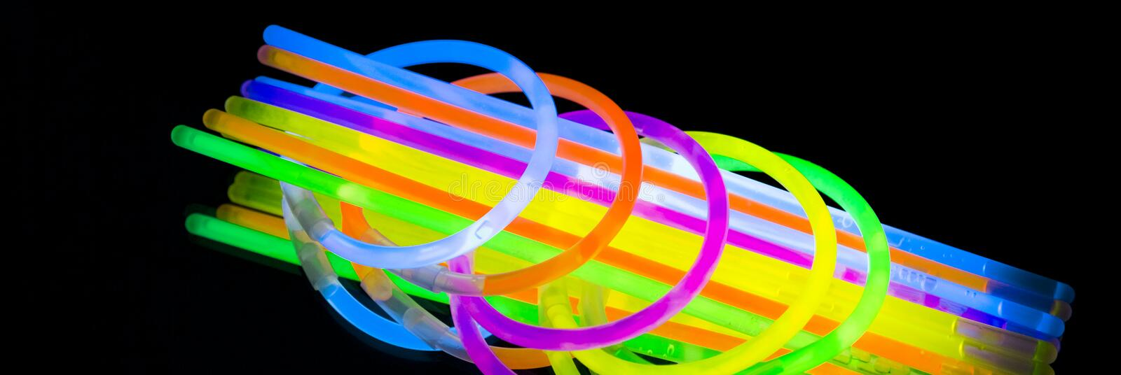 Colorful fluorescent light neon glow stick bracelet strap wristband and tubes on mirror reflection black background stock photos