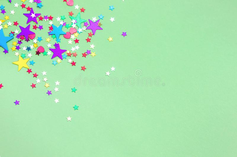 Colorful foil stars confetti sparse on trendy mint colored background. Simple holiday concept. Design template. Corner frame with copy space for text. Top view stock photography
