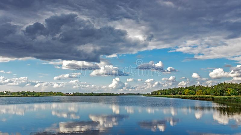 Colorful forest with green yellow trees and raining sky reflected in water surface lake, river . Sunny sky with grey clouds. autum royalty free stock photos