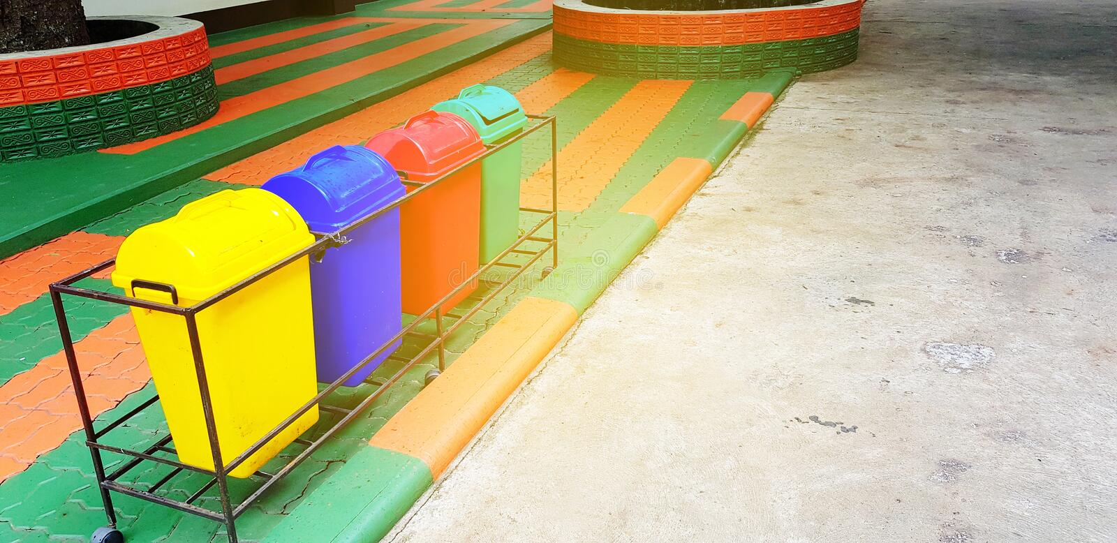 Colorful of four recycle bin or garbage for dumping waste on footpath with orange sunlight flare. And copy space - Cleaning city, Green world and Reduce royalty free stock photo