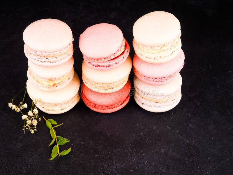 Colorful French or Italian macarons stack on black wood table with copy space for background. Dessert for served with afternoon royalty free stock images