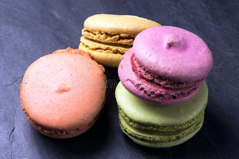 Colorful French macarons on a black background royalty free stock photo