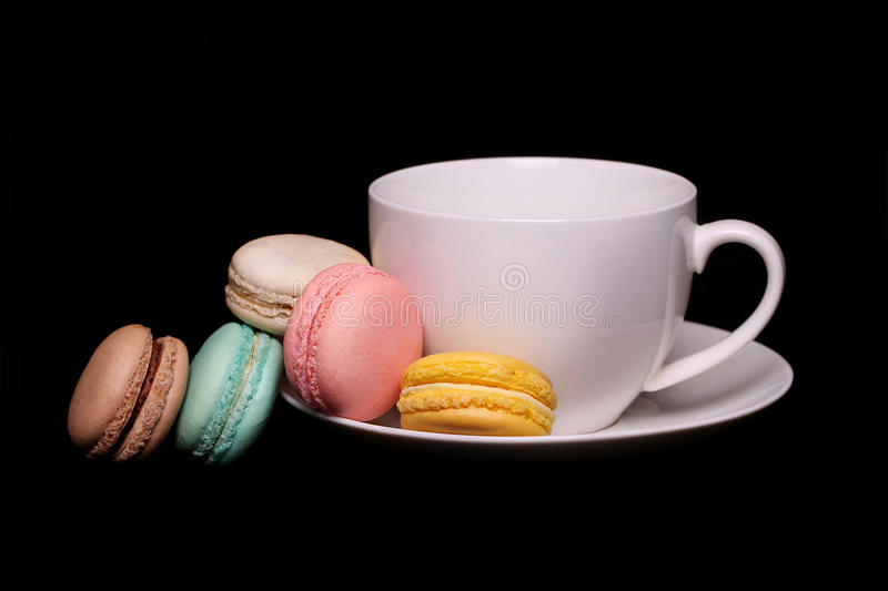 Colorful French Macarons with Cup of Tea over black royalty free stock photos
