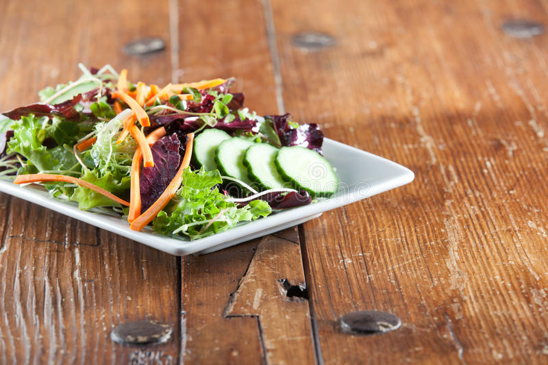 Colorful fresh arugula salad on rustic wooden table royalty free stock images