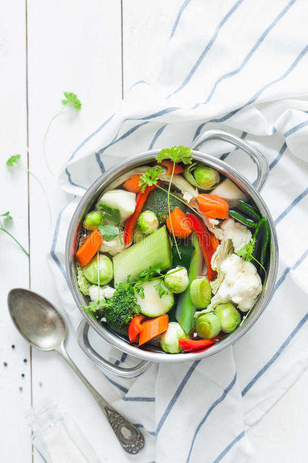 Colorful fresh clear spring soup - vegetarian stock. Various fresh vegetables in a pot - colorful fresh clear spring soup vegetarian bouillon or stock. Rural royalty free stock photo