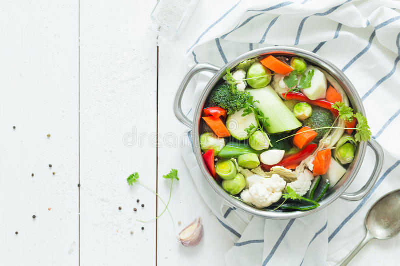 Colorful fresh clear spring soup - vegetarian stock. Various fresh vegetables in a pot - colorful fresh clear spring soup vegetarian bouillon or stock. Rural stock photos