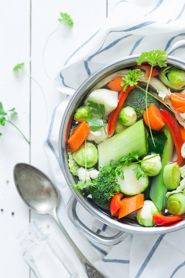 Colorful fresh clear spring soup - vegetarian stock. Various fresh vegetables in a pot - colorful fresh clear spring soup vegetarian bouillon or stock. Rural royalty free stock images