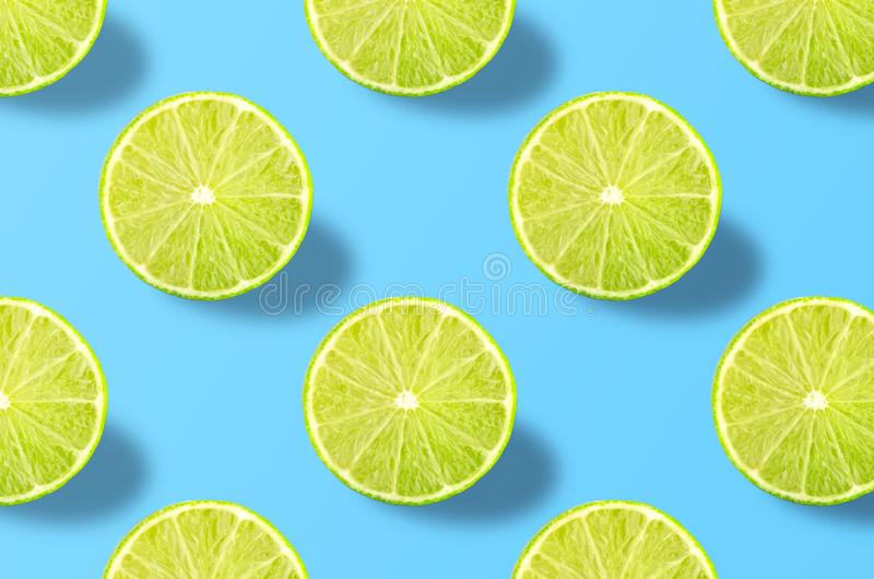 Vivid fruit pattern of fresh lime on colourful background. Colorful fresh slices lime texture on light blue background. From top view. full depth of field stock photos