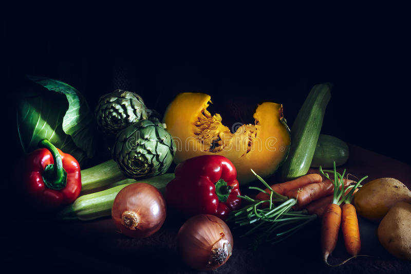 Colorful fresh vegetables on black background. Carrots, cabbage, pumpkin, onions, zucchini, potatoes, tomatoes, artichokes and re stock photography