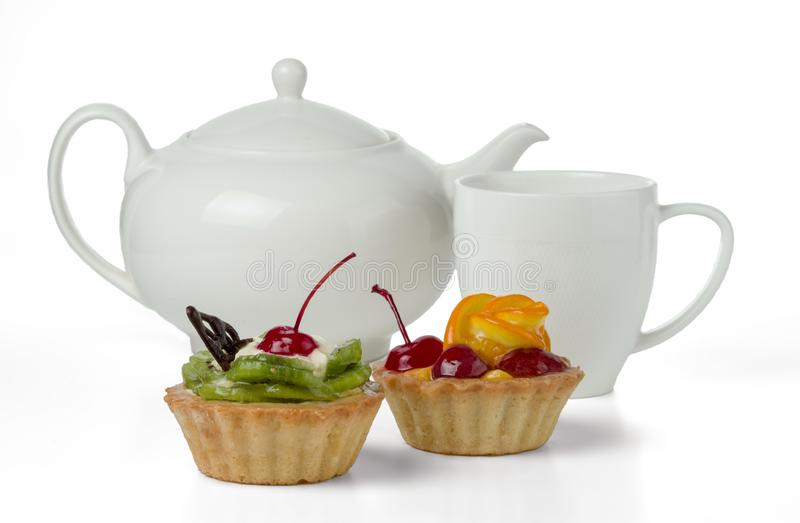 Colorful fruit cakes made with kiwi, orange, candied cherry, cream and chocolate isolated on a white background with a cup and a t stock photo