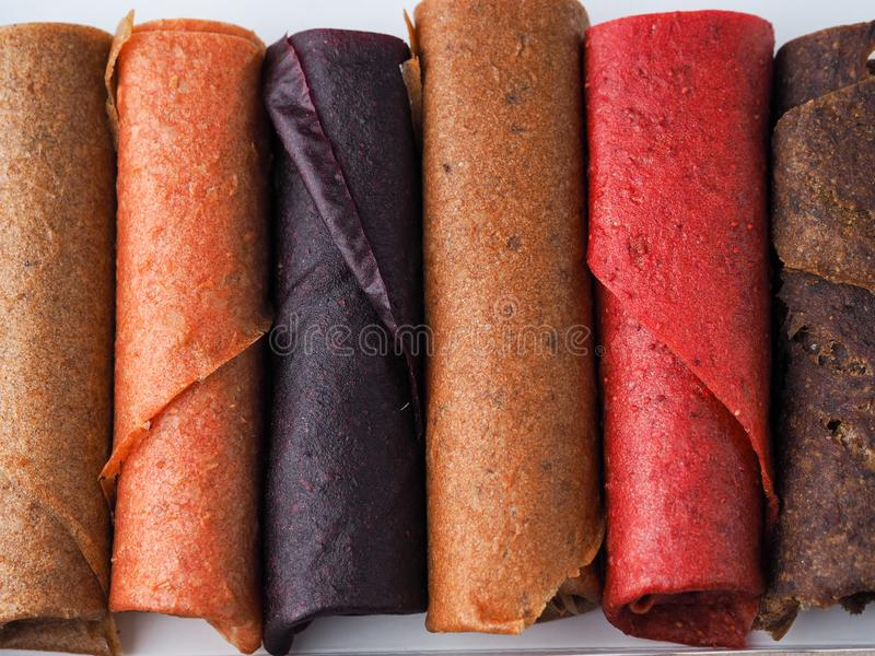 Colorful fruit leather rolls on white background stock photo