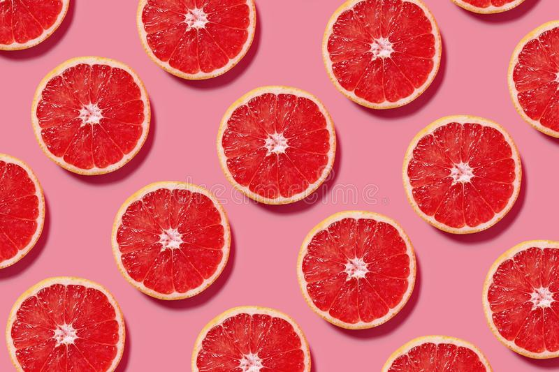 Colorful fruit pattern of fresh grapefruit slices on pink background. Minimal flat lay concept royalty free stock photos