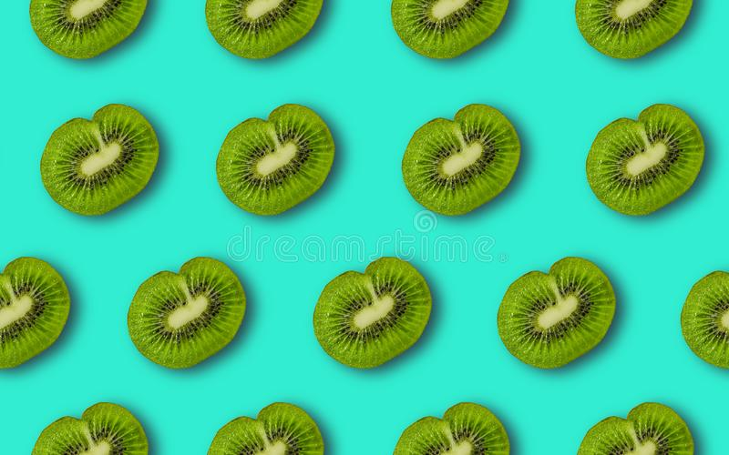 Colorful fruit pattern of fresh kiwi slices. On blue background. From top view. Minimal concept stock photos