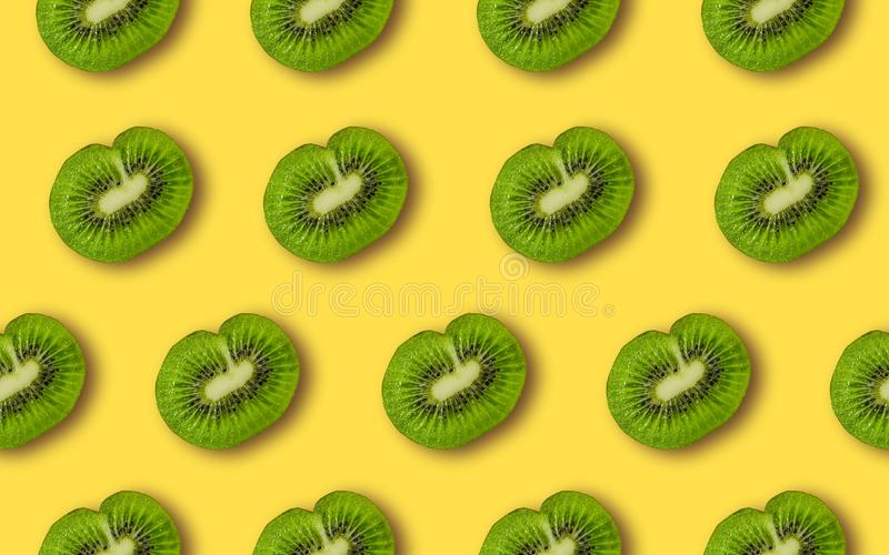Colorful fruit pattern of fresh kiwi slices. On yellow background. From top view. Minimal concept royalty free stock photo