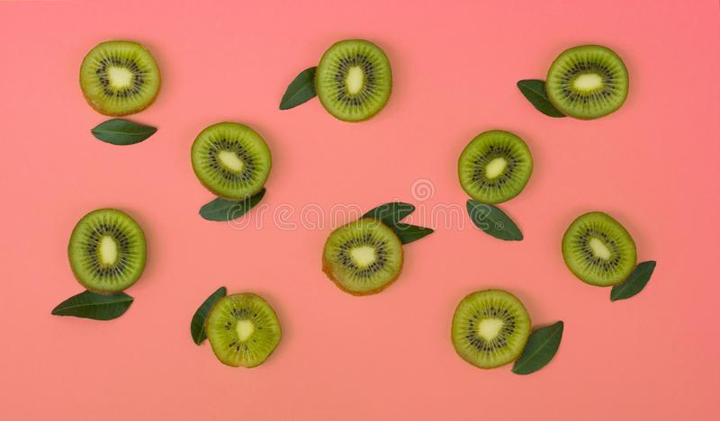 Colorful fruit pattern of fresh kiwi slices on pink background. From top view stock photography
