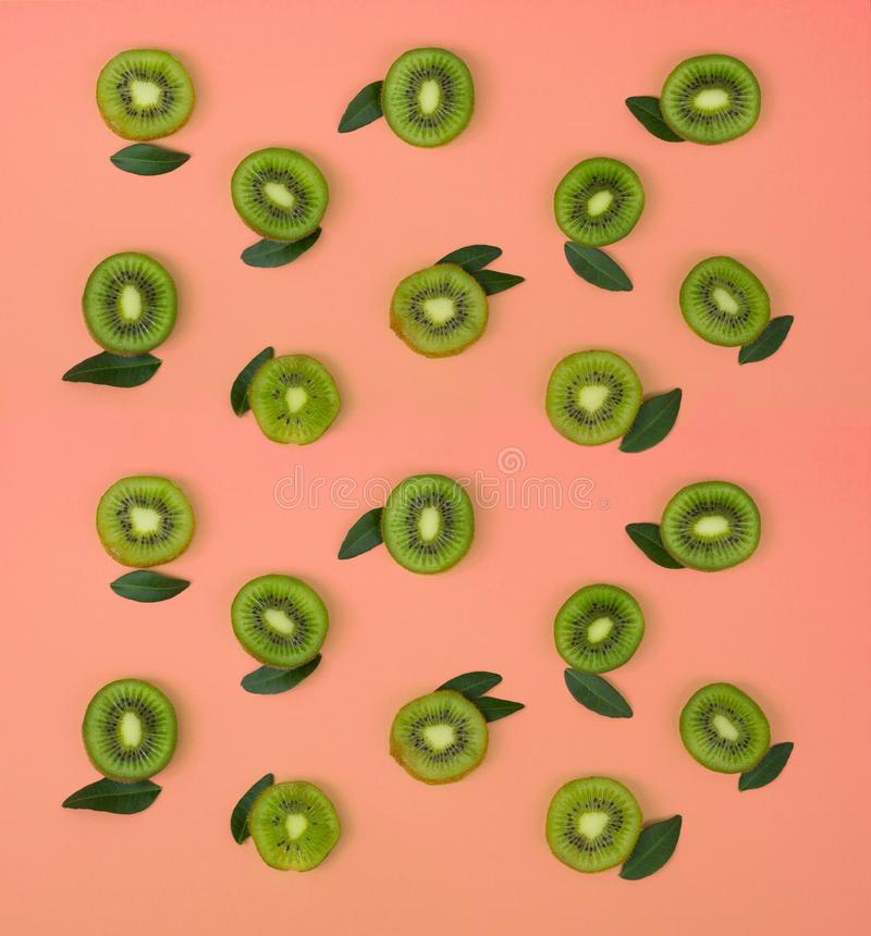 Colorful fruit pattern of fresh kiwi slices on pink background. From top view royalty free stock photo