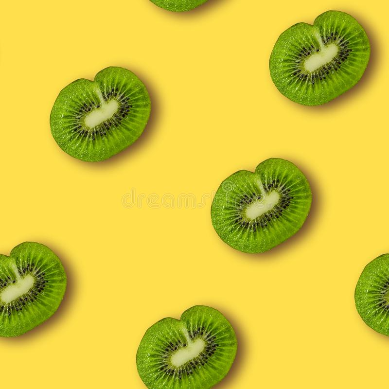 Colorful fruit pattern of fresh kiwi slices. On yellow background. From top view. Minimal concept royalty free stock image
