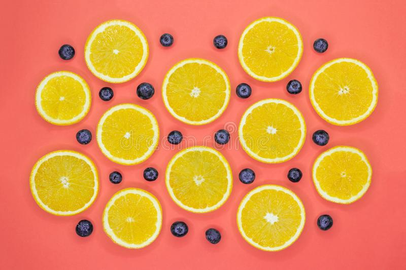 Colorful fruit pattern of fresh orange slices and blueberries on coral background stock images