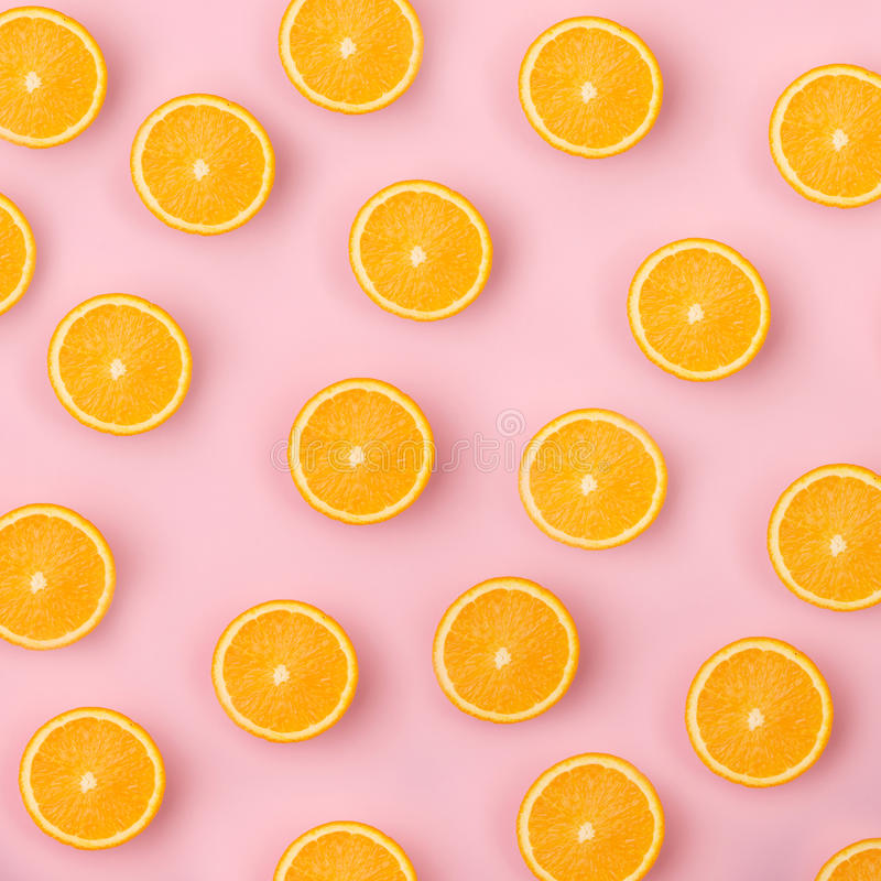 Colorful fruit pattern of fresh orange slices on pink background royalty free stock image