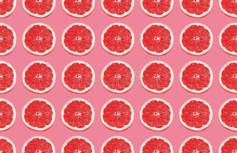Colorful fruit pattern of grapefruit slices on pink background. royalty free stock photography