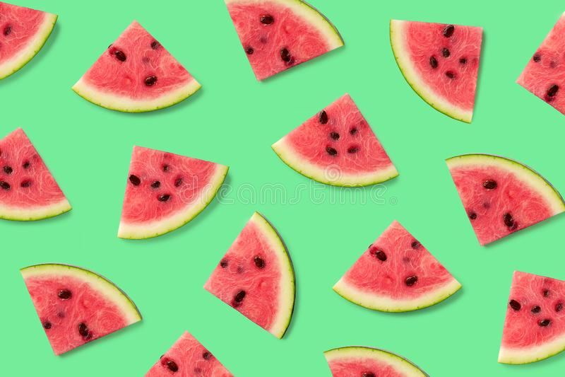 Colorful fruit pattern of watermelon slices. On green background. Top view. Flat lay stock photos
