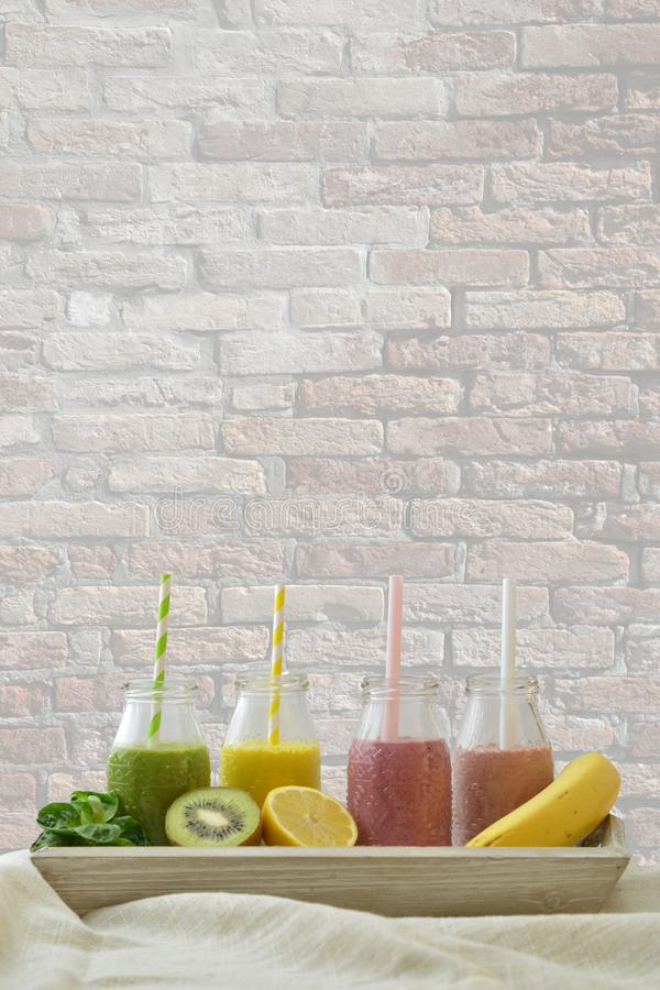 Colorful fruit smoothies in a row with fresh fruits in front of brick wall royalty free stock photos
