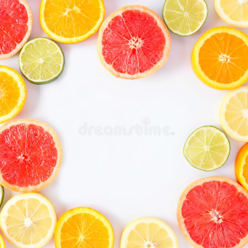 Colorful fruit square frame of citrus slices, top view over a white background. Colorful fruit square frame of fresh citrus slices. Top view, flat lay over a royalty free stock image