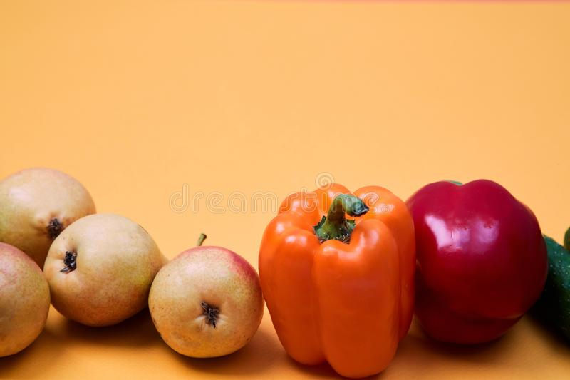 Colorful fruit and vegetables pattern or background. Composition of different ripe vegetables and pears on orange stock photo
