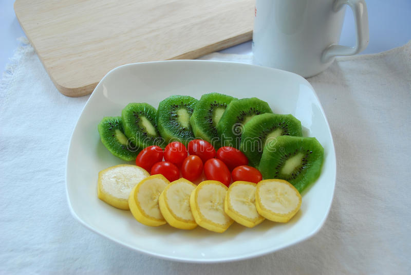 Colorful of fruits. Slice kiwi and banana with tomato decorated with cup and wood royalty free stock photography