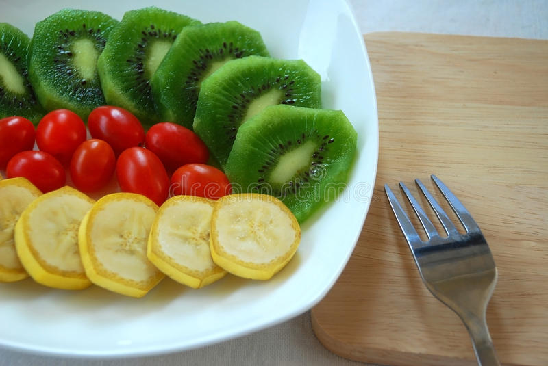 Colorful of fruits. Colorful of slice kiwi and banana with tomato decorated with fork and wood stock image