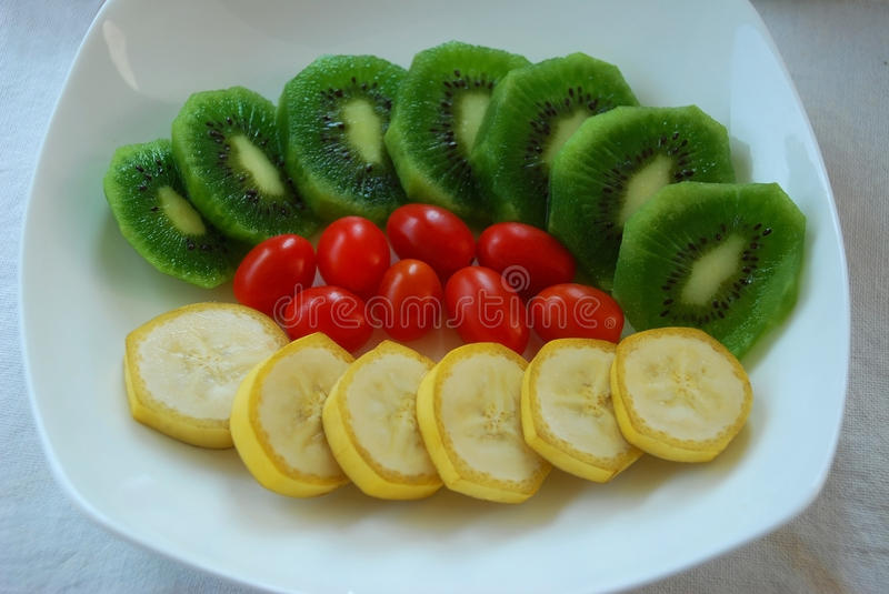 Colorful of fruits. Colorful of slice kiwi and banana with tomato in a plate stock photo