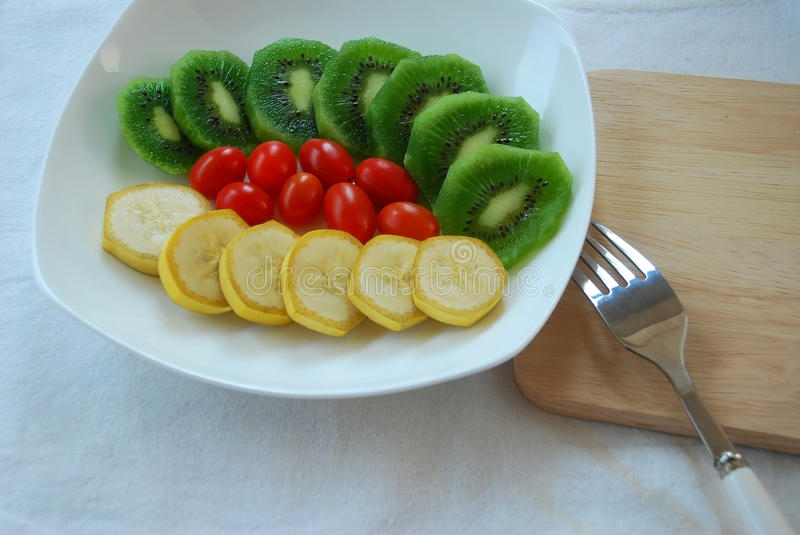 Colorful of fruits. Colorful of slice kiwi and banana with tomato ready to serve stock photos