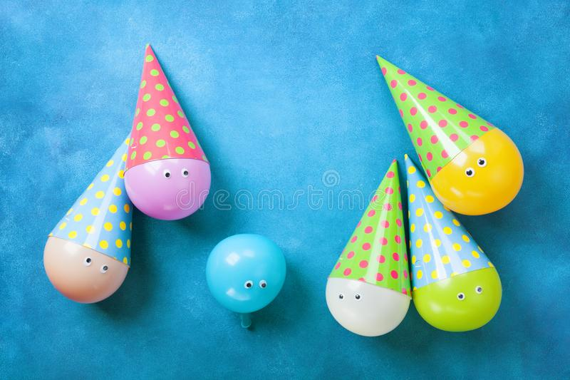 Colorful funny balloons in caps on blue table top view. Creative concept for birthday party background. Flat lay. royalty free stock photos