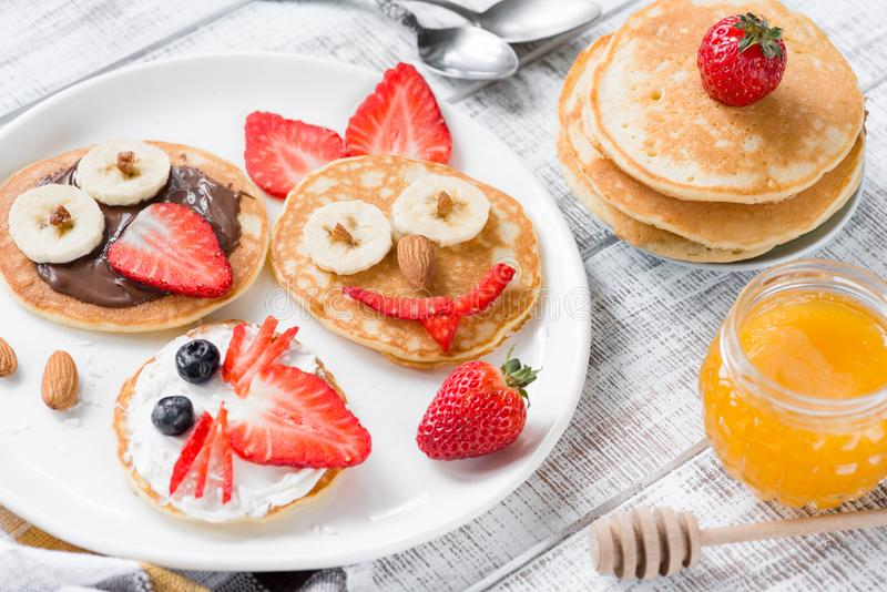 Colorful and funny breakfast for kids. Animal shaped pancakes on white plate. Creative food art, healthy breakfast for children concept royalty free stock photo