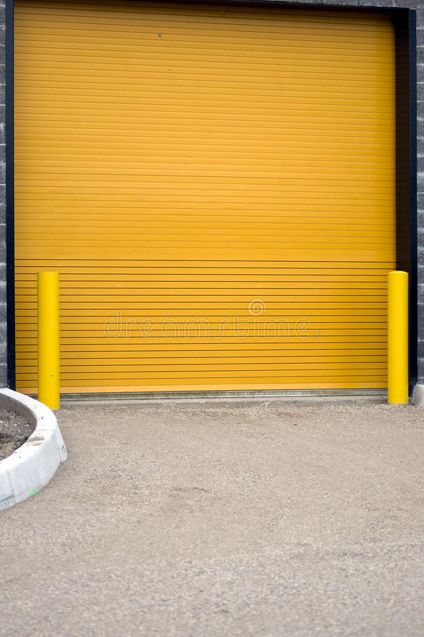 Colorful garage door. A colorful industrial garage door, with yellow barriers on either side. This door is actually on the side of a hockey rink, for Zamboni's stock photography