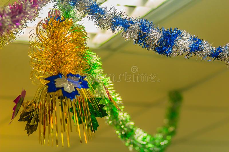Colorful garlands are hanging on the ceiling at the office to decoration prepare for Christmas and new year party cerebration. Colorful garlands are hanging on stock image