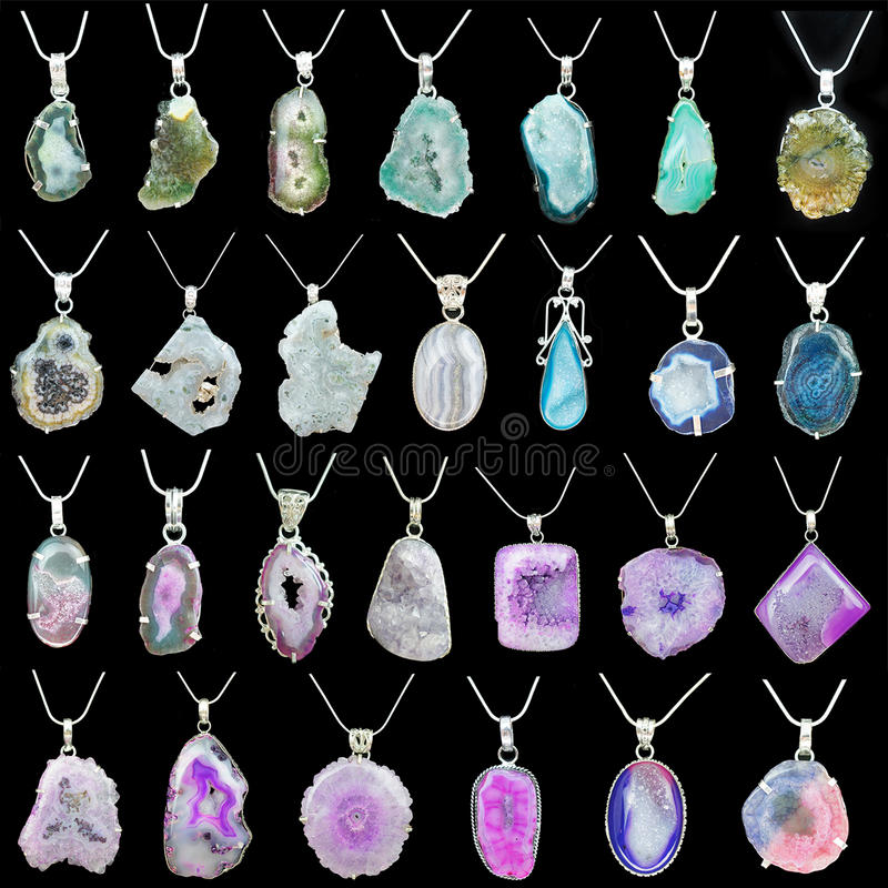 Colorful gemstone pendant necklaces. Display of colorrful gemstone pendants with chains on black background royalty free stock images