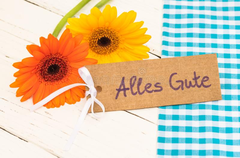 Gerbera daisy flowers and greeting card with german text, Alles Gute, means all the best royalty free stock photos