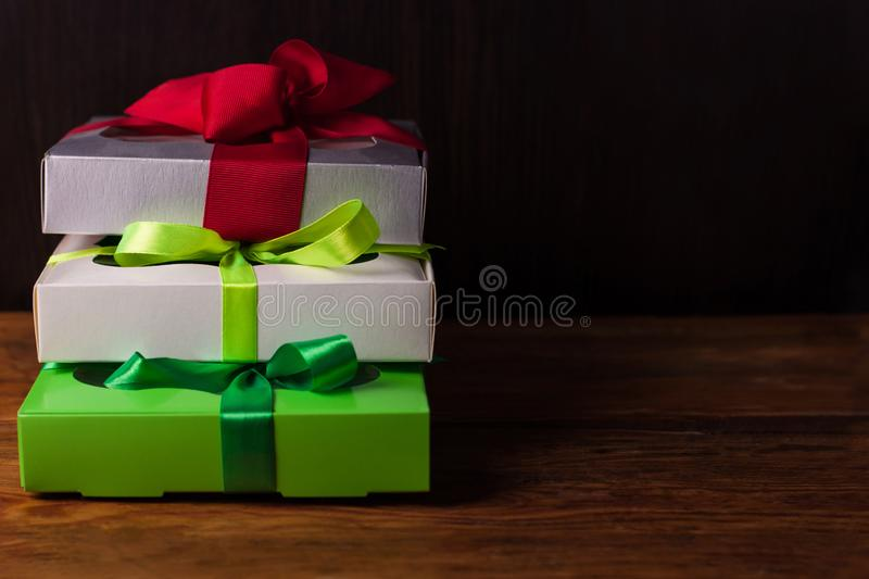 Colorful gift boxes with ribbon bows on a brown wooden background with copy space.Holidays,Christmas, New Year presents royalty free stock photography