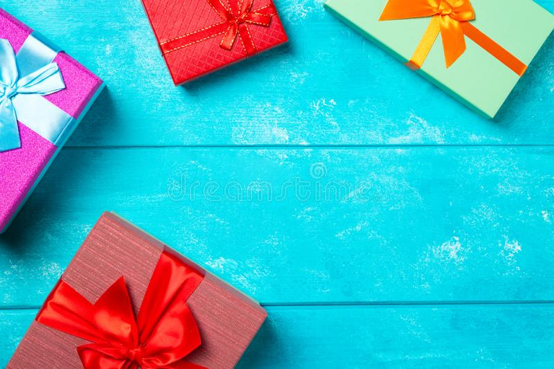 Colorful gift boxes with ribbons on nice blue wooden background. Copy space. Christmas or birthday celebration holiday theme royalty free stock images